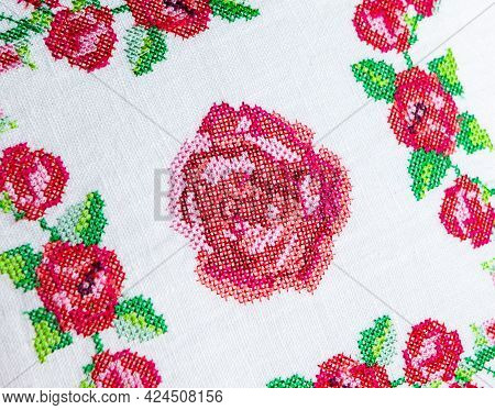 Cross-stitch Embroidery In The Form Of Roses On White Linen Fabric, Close-up. Embroidery Design.