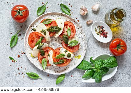 Caprese Salad With Juicy Tomatoes, Fresh Mozzarella And Pesto. Concept For A Tasty And Healthy Appet