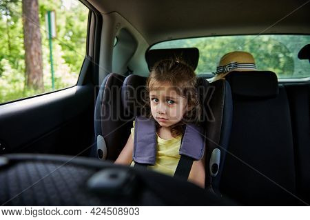 Safe Movement Of Children In The Car. Fastened Little Girl To Child Safety Seat Inside Car