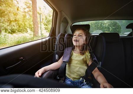 Safe Movement Of Children In The Car. Happy Girl In A Child Car Seat Wearing A Seatbelt While Travel