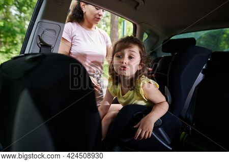 Adorable Sad Little Girl In The Car Seat. Mother Fastening Her Daughter With A Seat Belt For The Saf