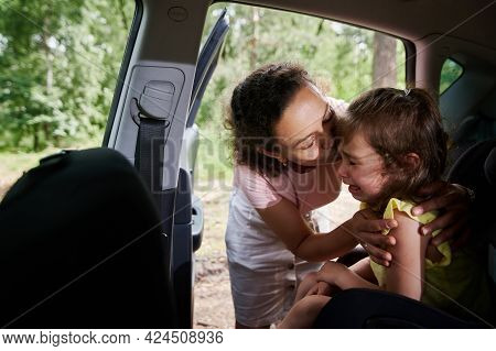 Woman Seats The Child In The Child\'s Car Seat. Mom Consoles Her Crying Baby Girl, Who Doesn\'t Want