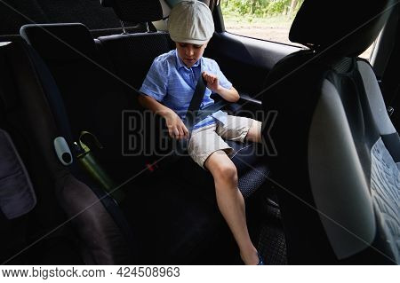 Safe Movement Of Children In The Car. An Adorable Boy Buckles The Seat Belt Of His Car Seat Inside T