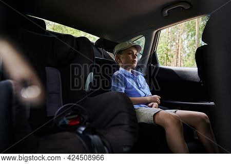 Schoolboy Sitting On A Safety Car Seat Before Fastening Ng For Safety Travel By Car