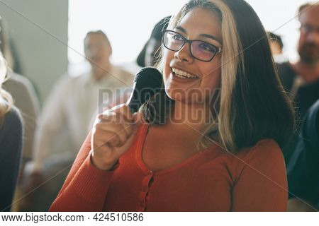 Closeup of a woman speaking on a microphone