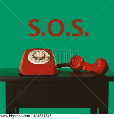 closeup of a red landline rotary dial telephone off-the-hook on a table and text SOS against a green background