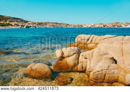 a panoramic view over Palau, in Sardinia, Italy, seen from the Spiaggia di Punta Nera beach, with its characteristic rock formations in the foreground