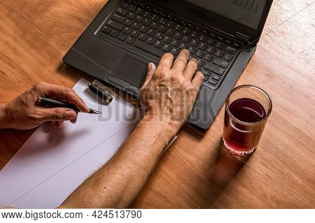 Man's Hands Write In Ink On White Paper And Type On A Laptop Keyboard. A Glass Of Juice