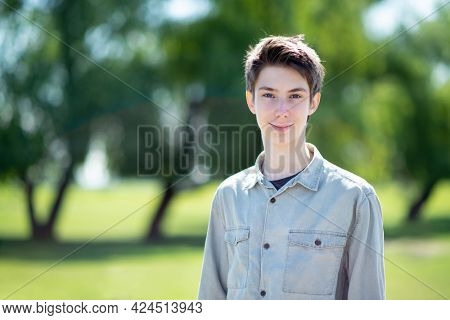 Handsome cheerful teen boy 15 years old smiling and looking at camera against blue sky, trees and green grass at spring meadow.