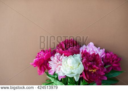 Peonies on brown background with copy space for your message. Seasonal flowers natural card, wallpaper or poster