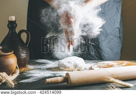 Male Hands With Flour Clap Over Dough Next To Clay Pot And Oil Bottle And Rolling Pin. Flour Splash