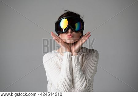 Female portrait in ski goggles with positive expressions. Beautiful young woman happy and excited expressing winning gesture over gray background. Girl and  snow winte sport equipment theme