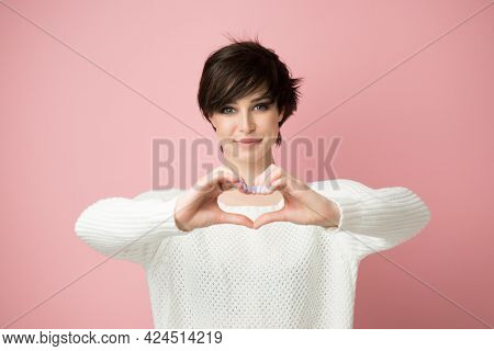 Young pretty woman looking at camera smiles and shows heart sign with her hands. Happy girl feels love and grateful. Human positive expressions