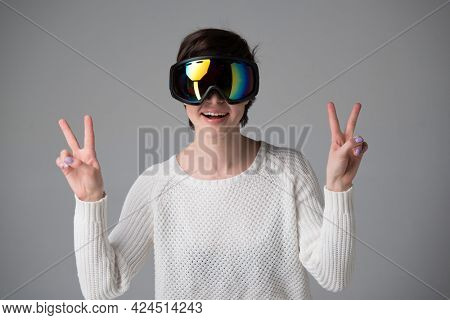Female portrait in ski goggles with positive expressions and victory sign, winning gesture over gray background, snow winter sport equipment theme