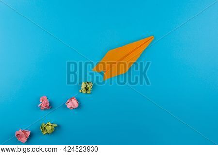 Flat lay of color paper plane on blue color paper background. Business for innovative solutionor air travel concept