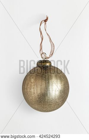 A shiny gold ball Christmas ornament isolated on gray background
