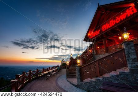 Ustron, Poland - June 4, 2021: A beautiful sunset over Dwór Skibowki restaurant on the top of Rownica peak in the Silesian Beskids, Poland