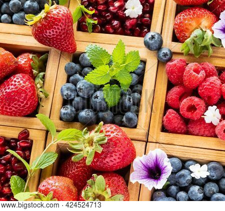 Close Up View Of A Wooden Compartment Box Filled With Various Berries.
