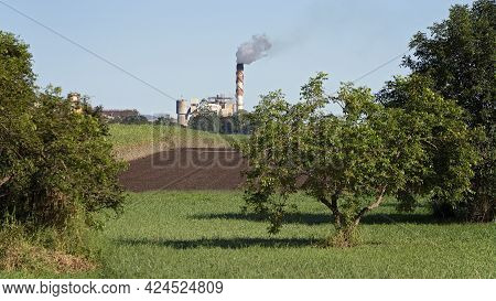 A Working Smoking Sugar Cane Mill Viewed Across A Paddock With Trees In The Foreground During Crushi