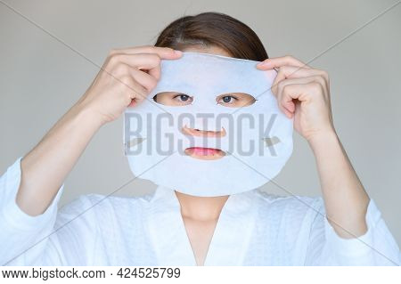 Portrait Of Young Woman Holding Facial Mask Befor Applying To Enhance Her Skin And Looking To Camera