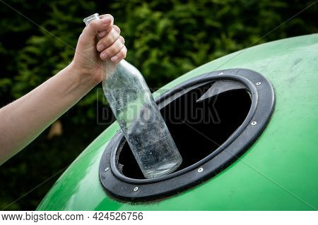 Throwing Empty Glass Bottle Into Green Recycle Bin Garbage Container. Waste Sorting And Recycling Co