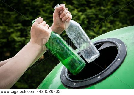 Throwing Two Empty Glass Bottle Into Green Recycle Bin Garbage Container. Waste Sorting And Recyclin