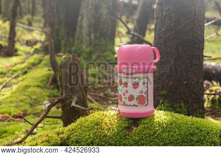 Children's Pink Thermos. Thermos Standing On Moss. Thermos For Drinks In The Forest. Hot Tea In A Th