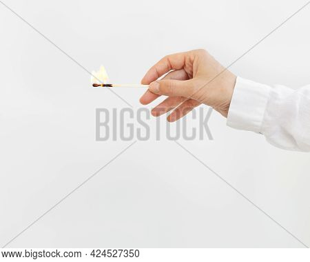 Female Hand Holds Lit Match On Light Background. Wooden Matchstick With Fire. Fire Hazard Concept.