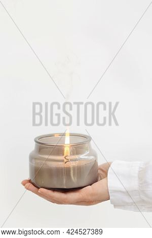 Female Hand Holds Lit Fragrant Candle In Glass Jar With Natural Ingredients On Light Background With