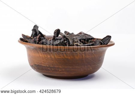 Dried Dog Treats In A Brown Clay Bowl On A White Background. Thin Slices Of Dehydrated Beef Kidneys.