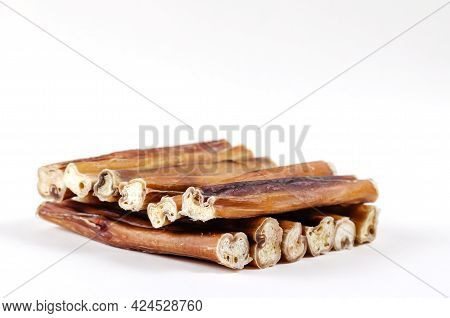 Natural Chewy Treats For Dogs On A White Background. Carefully Stacked 5-inch Bully Sticks.  Helpful