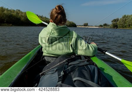 Girl In Front Of The Boat. The Girl Is Rowing With An Oar. The View Of The Girl From Behind. Girl In