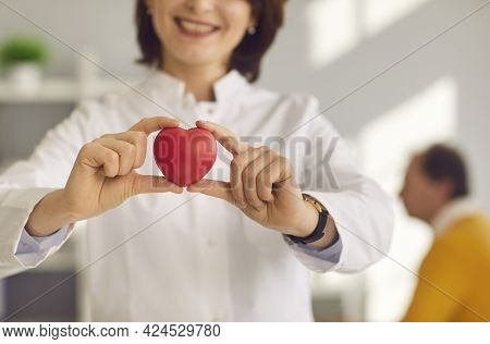 Close Up Of A Small Red Heart That Is Held In The Hands Of A Smiling Female Cardiologist.