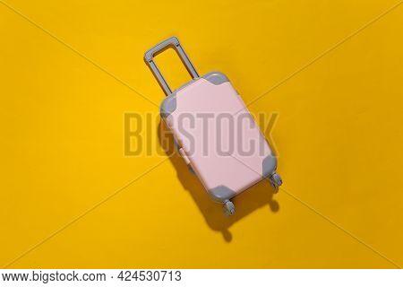 Travel Minimalism. Mini Plastic Travel Suitcase On Yellow Background With Deep Shadow. Minimal Style