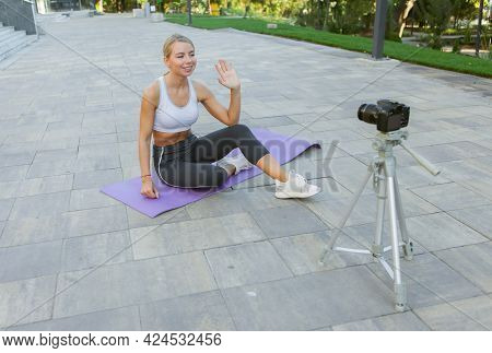 Sport Blog. Attractive Young Sports Woman Greets Her Followers Outdoors, Records On Camera On Tripod