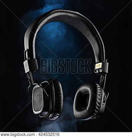 Audio Headphones On A Black Background. Black Headphones And Blue Smoke. Advertising Photo Of Headph