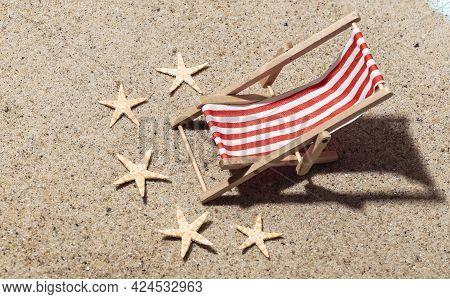 Summer Beach Travel Vacation Concept. Mini Beach Deck Chair On Sand With Starfish At Bright Sunny Da