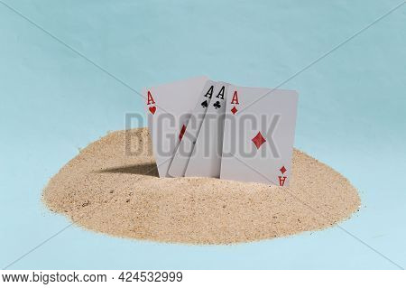 Four Aces Stuck In Sand On A Blue Studio Background