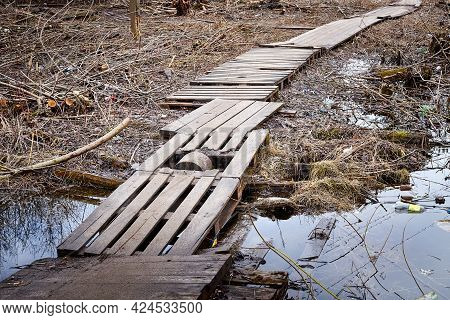 A Wooden Sidewalk Goes Through Muddy Wet Countryside Road. A Path On Wet Clay.