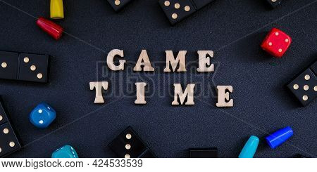 Text Game Time Spelled Out In Wooden Letter. Surrounded By Dice, Dominoes Other Game Pieces On Black