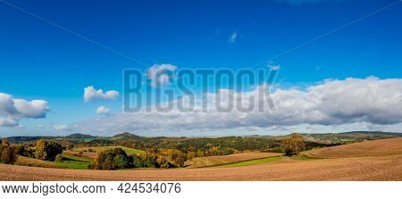 Panorama of foothill valley with plowed field in the spring