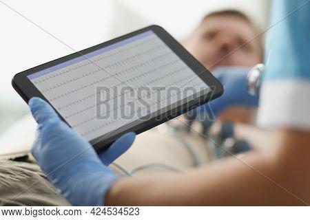 Cardiologist Examines Patient Electrocardiogram On Tablet Closeup
