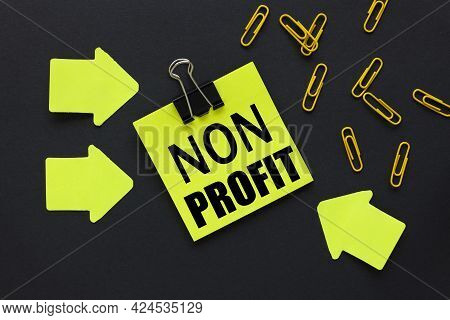 Non Profit. Text On A Black Background, On A Bright Yellow Sticker, Near Bright Yellow Stickers And