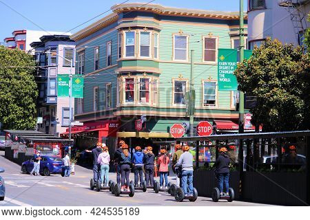 June 8, 2021 In San Francisco, Ca:  Tour Group On Riding On Scooter Rentals Surrounded By Historical