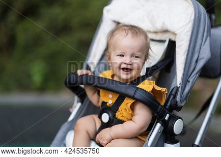 Sweet Caucasian Baby Girl Ten Months Old Sitting In Stroller Outdoors. Little Child In Pram. Infant