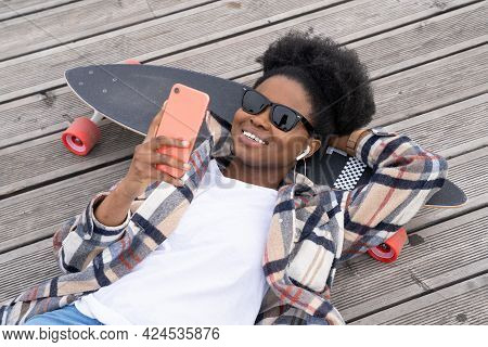 Happy African Girl Skater Text In Smartphone Lying In Modern Urban Space On Longboard. Carefree Youn