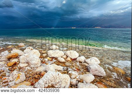 Rocky beach covered with evaporated salt. Gloomy sky with dark thunderclouds. Magnificent exotic resort for treatment and relaxation. The Dead Sea is a closed salt lake. Israeli coast