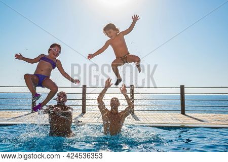 Two Happy Kids with Their Fathers Having Fun in the Pool. Jumping and Making Splashes. Enjoying Summer Holidays on the Beach Resort.