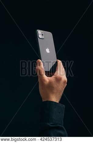 The Male Hand Holds An Iphone 11 On A Black Background, The Apple Logo Is Deployed To The Camera.