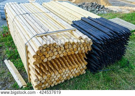 Two Pallets With Long Round Natural Wooden Fence Posts With Tarred And Sharpened Ends